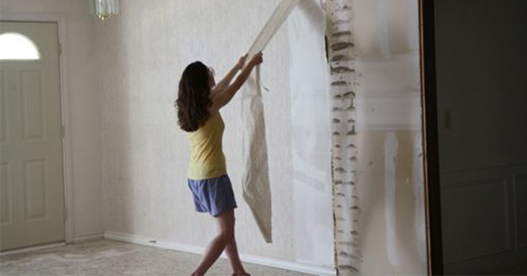 A girl is removing old wallpaper